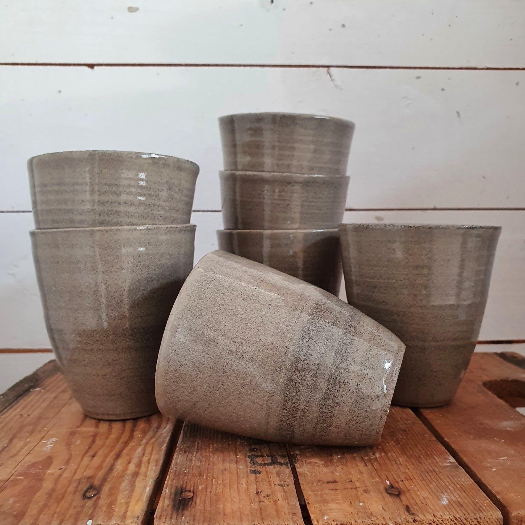sandfärgade kaffekoppar utan öra i keramik