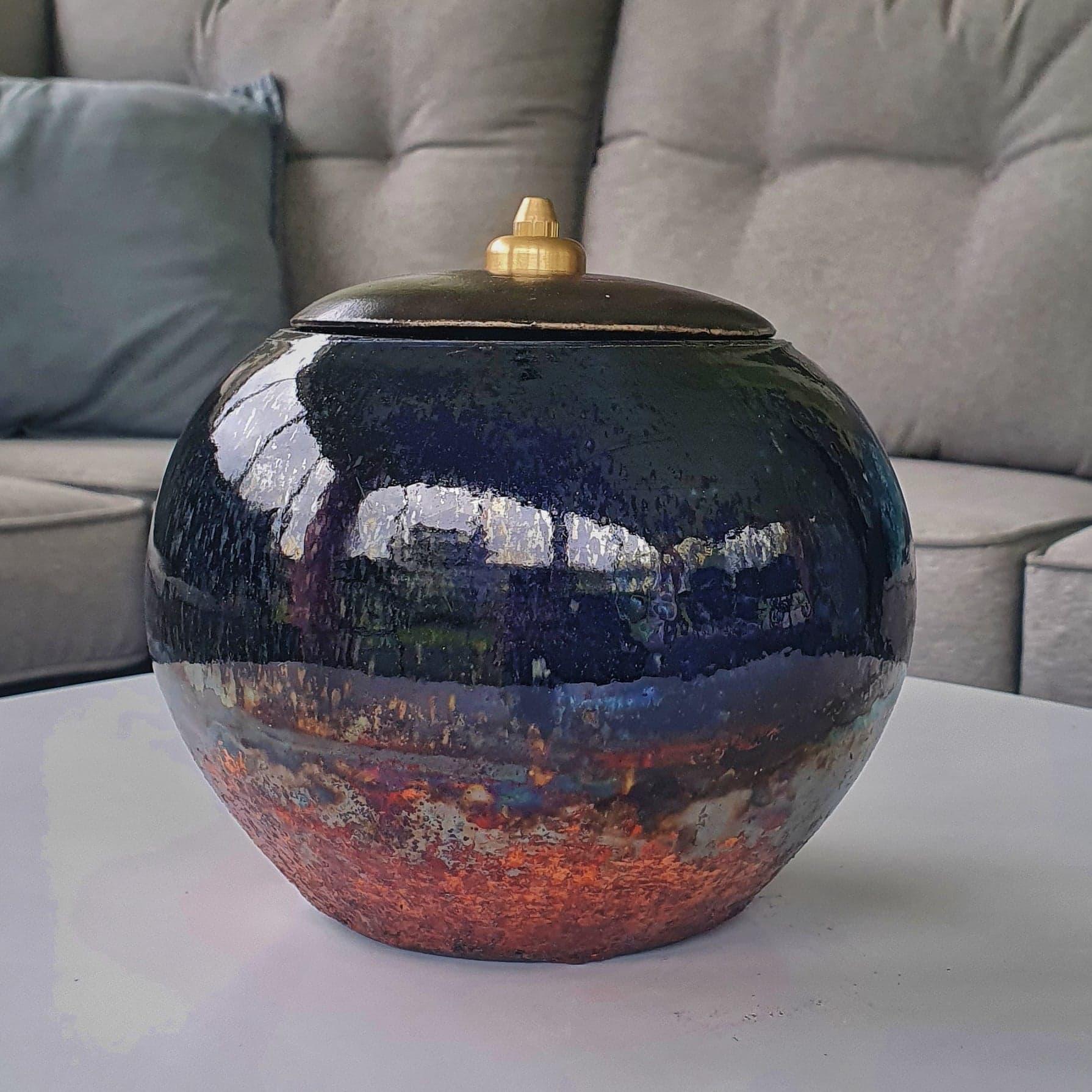Klotformad akubränd oljelampa. Blåsvart med kopparutfällningar och skiftningar i blått, silver, grönt och rött